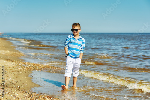 Foto Murales A boy on a walk along the sea coast . Child in white trousers and t-shirt