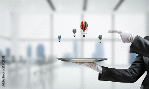 Hand of waiter presenting balloons on tray.