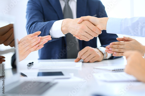 Leinwanddruck Bild Group of business people or lawyers shaking hands finishing up a meeting , close-up. Success at negotiation and handshake concepts