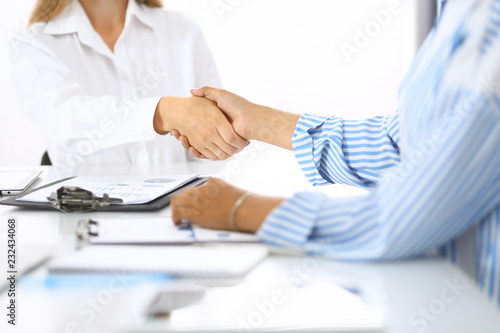 Business handshake at meeting or negotiation in office. Partners shaking hands while satisfied because signing contract or financial papers. Best client service, casual style. Success concept