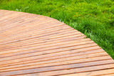 Turning new wooden boardwalk over grass - 232439046