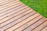 New shiny wooden boardwalk over park lawn - 232439062