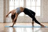 Young sporty yogi woman practicing yoga, doing Wild Thing, Flip-the-Dog exercise, Camatkarasana pose, working out, wearing sportswear, black pants and top, indoor full length, white yoga studio © fizkes