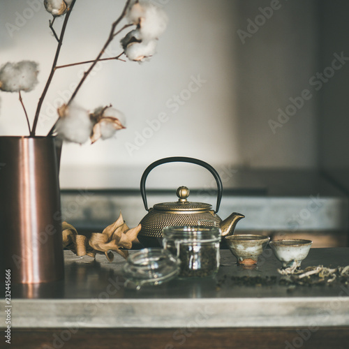 Leinwandbild Motiv Tea ceremony. Golden iron teapot and japanese ceramic cups full of green tea drink on grey concrete kitchen counter, selective focus, square crop. Cold winter morning at home