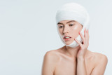 nude woman with bandages on head after plastic surgery isolated on white - 232448201