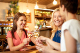 people, celebration and lifestyle concept - happy women drinking wine and clinking glasses at bar or restaurant