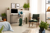 Urban jungle in bright bedroom interior with retro armchair and workspace with all in one computer and globe - 232451241