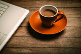 orange cup of coffee near laptop computer on wooden table. Side view - 232455837