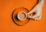 female hand holding an orange cup of coffee with milk on polka dot background. Above view - 232455850