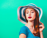 style redhead girl with makeup in blue hat on green background isolaed - 232455865