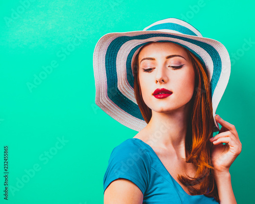 Foto Murales style redhead girl with makeup in blue hat on green background isolaed