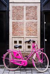 Pink retro bike against brick house entrance