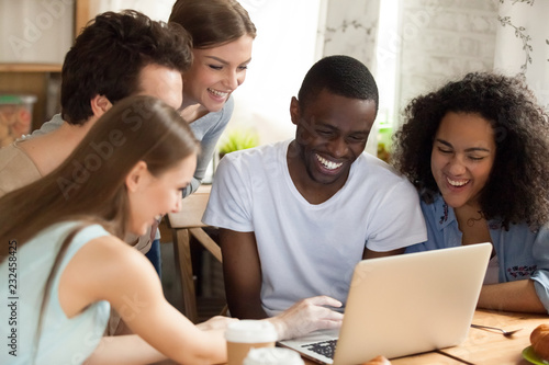 Leinwandbild Motiv Black african guy with diverse friends watching comedy movie funny videos online using computer sitting together at desk. Friendship between multiracial people and leisure free time activities concept