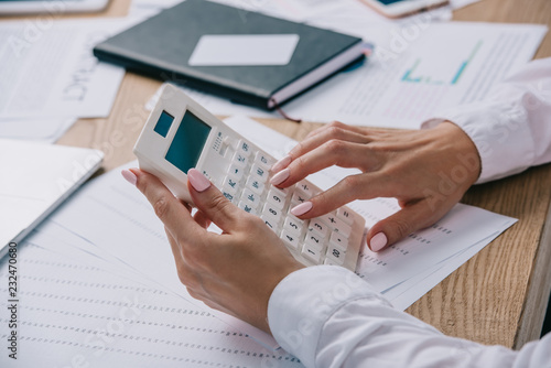 Wall mural cropped shot of businesswoman making calculations on calculator at workplace with documents