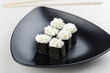 Sushi Maki on a black plate. Triangular black plate with sushi on a light background.