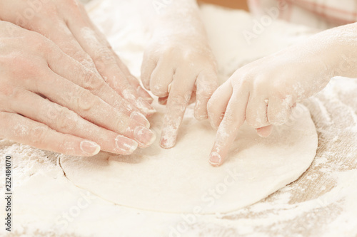Wall mural Mother and child hands prepares the dough with flour for bread or pizza. Bakery background.
