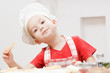 Little cheerful boy chef cooks and eats pizza