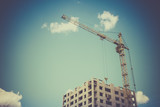 Construction crane and building against blue sky - 232485294