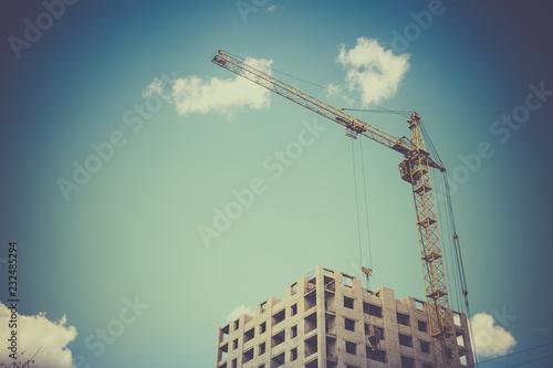 Budowa żuraw i budynek przeciw niebieskiemu niebu