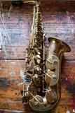 Saxofón alto posado en una mesa de madera manchada con pinturas.