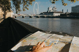 Thames River and London Eye viewed from Victoria Tower Gardens, while tourist uses a London city map to locate them. - 232501871