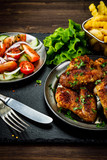 Roast chicken wings with french fries and vegetable salad  - 232504407