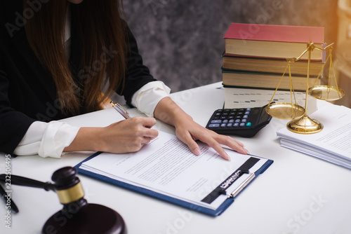 Women lawyer working with contract papers and wooden gavel on tabel in courtroom. justice and law ,attorney, court judge, concept. © ordinary042