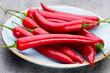 Leinwandbild Motiv Chili cayenne pepper on grey background.