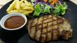 Pork steak in a black dish French fries, green salad, purple cauliflower, Close up. . - 232509686