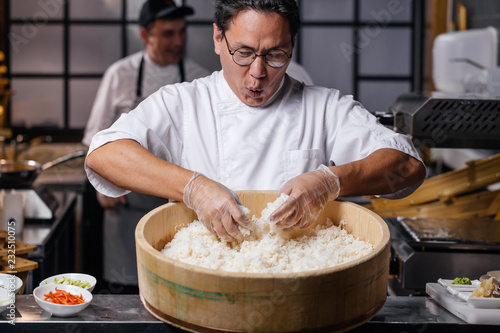 Wall mural young emotional man is happy to prepare rice. funny chef is singing songs while cooking rice for sushi. close up photo