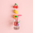 Flying fruits and glass with drinking straw abstract on rose. - 232522043