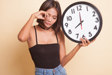 Sleepy young Asian woman with a clock in the morning. - 232527259