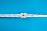 White ship ropes connected by reef knot on blue - 232537412