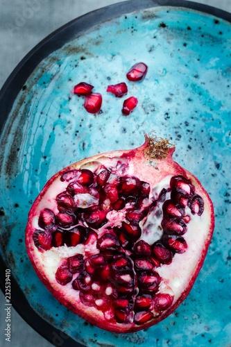 Foto Murales delicious, juicy half cut pomegranate on a blue handmade ceramics plate