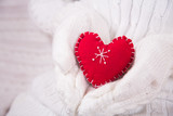 Hands in white knitted mittens holding red decorative heart. - 232553694