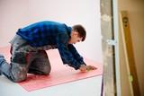 Man worker installing foam primer on floor - 232559073