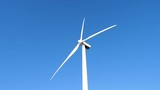 Close up view of Wind Turbine spinning against blue sky - 232577896