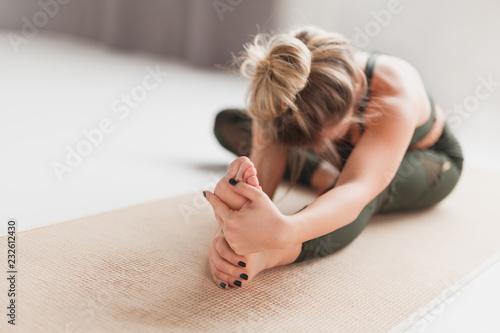 Leinwanddruck Bild Young woman performing Janusirsasana exercise