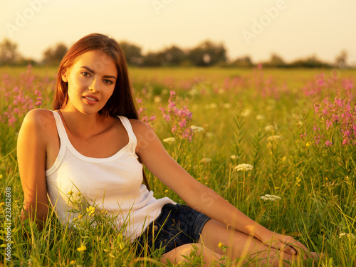 Foto Murales Beautiful young woman on nature over summer field background