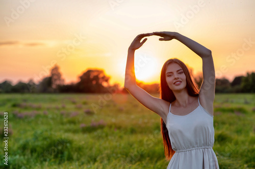 Foto Murales  Pretty joyful  woman  with raised hands over sunset background.