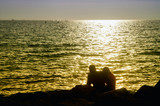 Silhouettes of men and women sitting on the shore of the gulf against the backdrop of the waves and the setting evening sun with golden lighting - 232615696