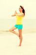 Leinwanddruck Bild - Young woman making yoga exercises on the beach