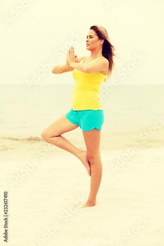Leinwanddruck Bild Young woman making yoga exercises on the beach