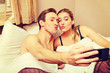 Leinwanddruck Bild - Young couple making selfie while lying in bed