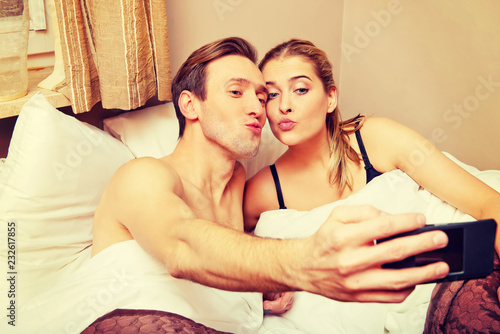 Leinwanddruck Bild Young couple making selfie while lying in bed