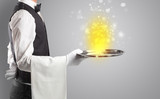 Elegant young waiter serving mysterious light on tray