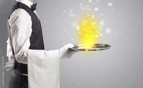 Leinwanddruck Bild Elegant young waiter serving mysterious light on tray