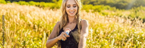 Mosquito repellent. Bug spray anti insects for zika virus. Woman spraying insect repellent putting on skin outdoor in nature using spray bottle BANNER, LONG FORMAT - 232633890