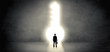 Businessman standing alone in front of a big keyhole