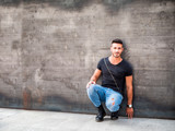 Handsome young man standing against concrete wall, looking at camera, wearing black t-shirt and jeans. Full length shot